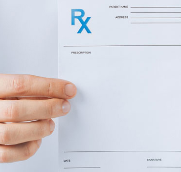 male doctor holding rx paper in hand